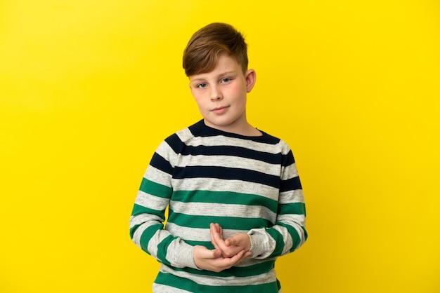 Маленький рыжий мальчик, изолированные на желтом фоне смеясь