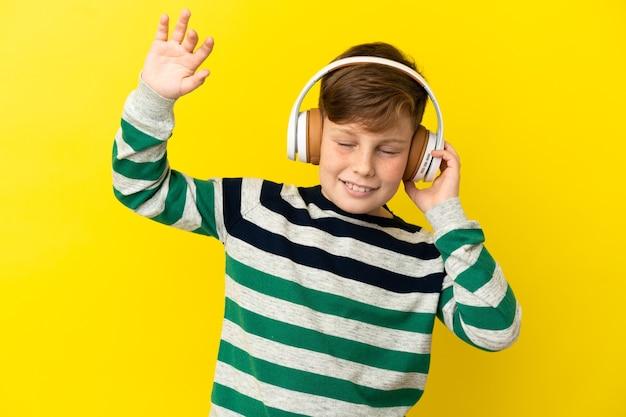 노란색 배경에 고립 된 작은 빨간 머리 소년 음악을 듣고 춤