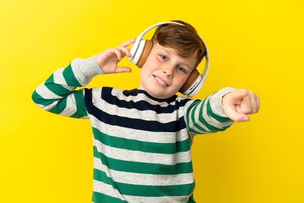 노란색 배경에 격리된 작은 빨간 머리 소년은 음악을 듣고 앞을 가리키고 있습니다.
