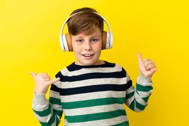 노란색 배경에 고립 된 작은 빨간 머리 소년은 바위 제스처를 만드는 음악을 듣고
