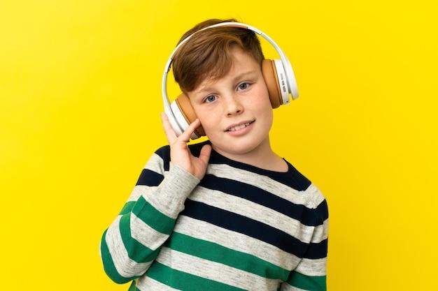 音楽を聞いて黄色の背景に分離された小さな赤毛の少年