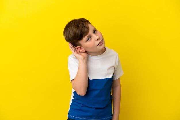 노란색 배경에 격리된 작은 빨간 머리 소년은 귀에 손을 대고 무언가를 듣고 있습니다.