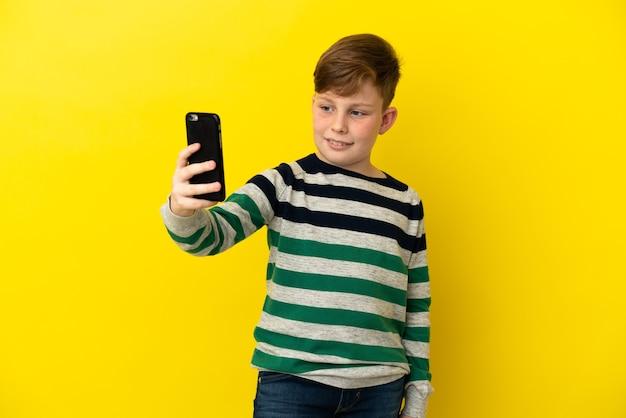 Маленький рыжий мальчик, изолированные на желтом фоне, делая селфи
