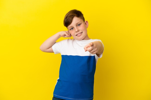 노란색 배경에 격리된 작은 빨간 머리 소년은 전화 제스처를 만들고 앞을 가리키고 있습니다.