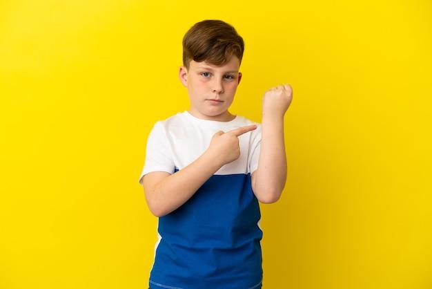 Маленький рыжий мальчик изолирован на желтом фоне, делая жест опоздания