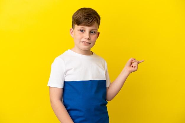 노란색 배경에 고립 된 작은 빨간 머리 소년은 손가락을 옆으로 가리키는