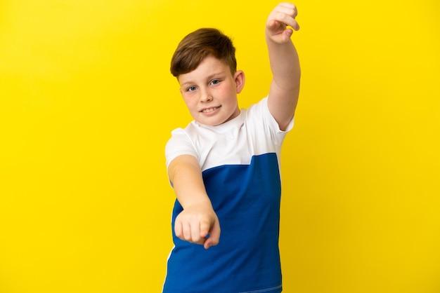 행복 한 표정으로 앞을 가리키는 노란색 배경에 고립 된 작은 빨간 머리 소년