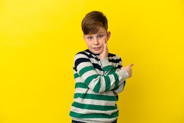 노란색 배경에 격리된 작은 빨간 머리 소년은 제품을 제시하고 무언가를 속삭이기 위해 측면을 가리키고 있습니다.