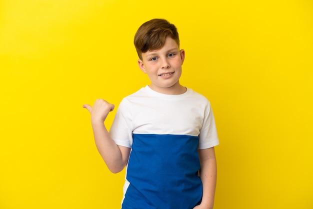 제품을 제시하기 위해 측면을 가리키는 노란색 배경에 고립 된 작은 빨간 머리 소년