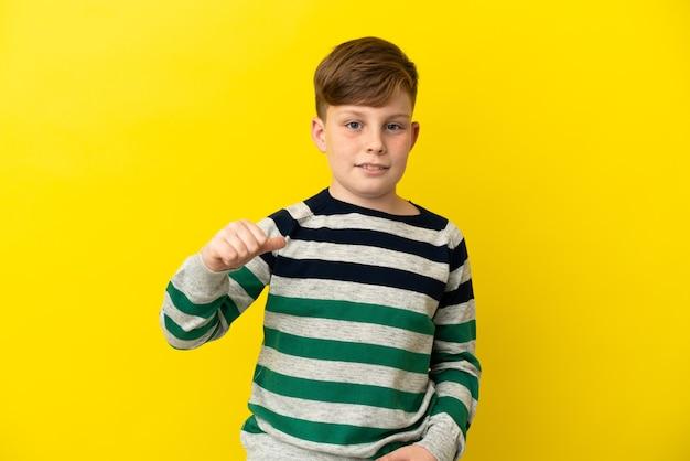 Маленький рыжий мальчик, изолированные на желтом фоне, гордый и самодовольный