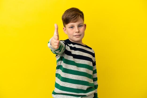 Маленький рыжий мальчик изолирован на желтом фоне, пожимая руку для заключения хорошей сделки