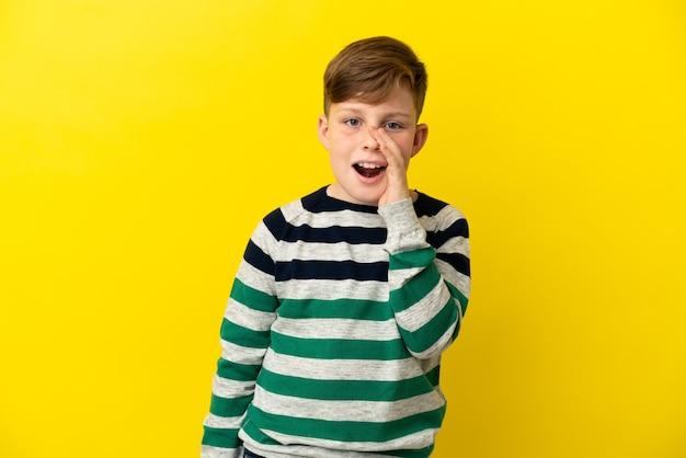 Маленький рыжий мальчик, изолированные на желтом фоне, кричит с широко открытым ртом