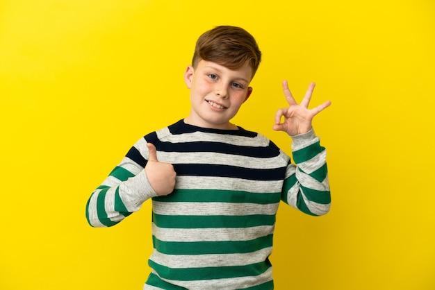 확인 표시와 제스처를 보여주는 노란색 배경에 고립 된 작은 빨간 머리 소년