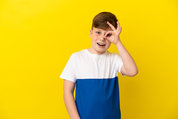 Маленький рыжий мальчик, изолированные на желтом фоне, показывает пальцами знак ок