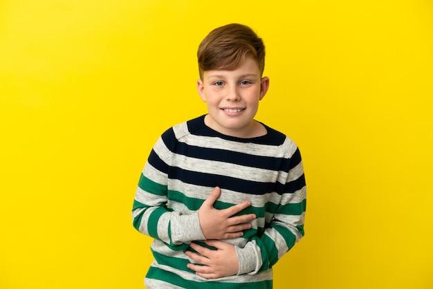 Маленький рыжий мальчик, изолированные на желтом фоне, много улыбаясь Premium Фотографии