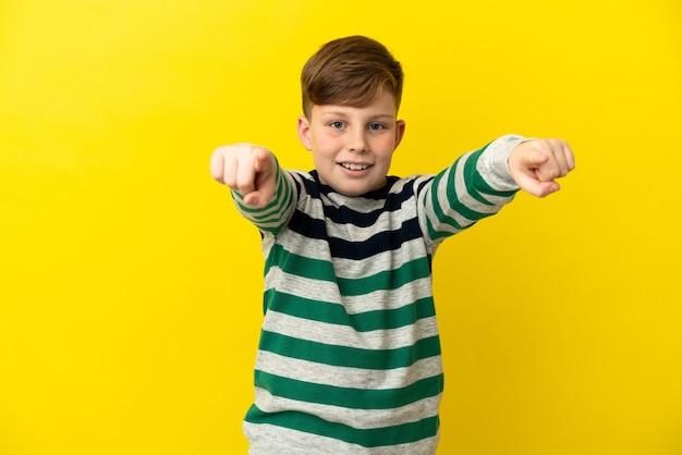 노란색 배경에 고립 된 작은 빨간 머리 소년 놀고 앞을 가리키는
