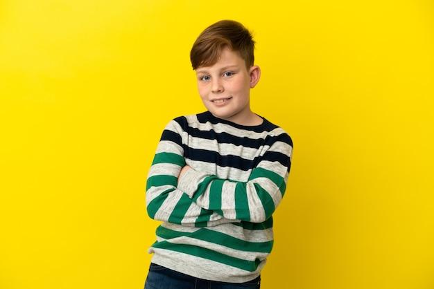 Маленький рыжий мальчик изолирован на желтом фоне со скрещенными руками и смотрит вперед