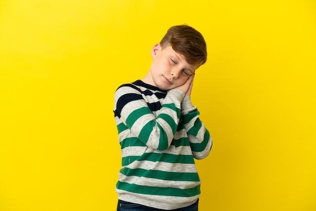 黄色い表面に孤立した小さな赤毛の少年が愛らしい表情で睡眠ジェスチャーをしている