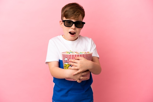 Little redhead boy isolated on pink background surprised with 3d glasses and holding a big bucket of popcorns
