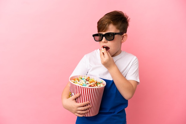 Little redhead boy isolated on pink background with 3d glasses and holding a big bucket of popcorns while looking side