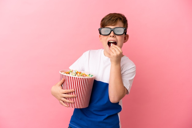 Little redhead boy isolated on pink background with 3d glasses and holding a big bucket of popcorns