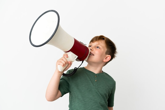 Little redhead boy isolated on white background shouting through a megaphone to announce something in lateral position