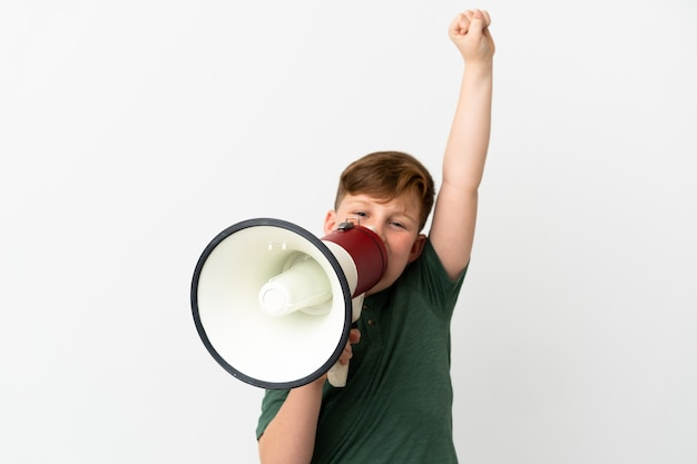 Little redhead boy isolated on white background shouting through a megaphone to announce something