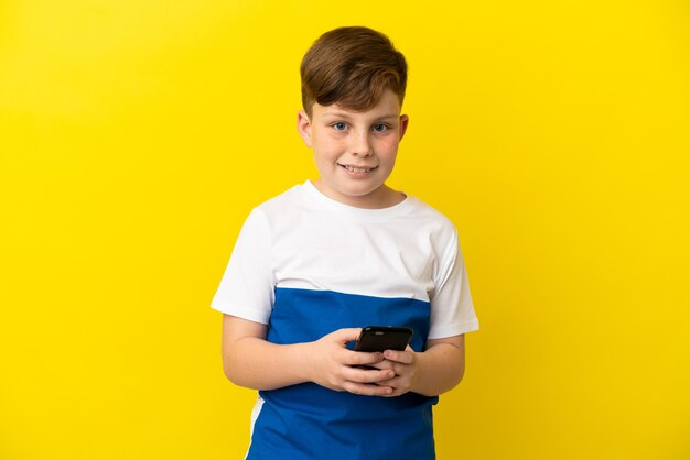 Little redhead boy isolated on yellow background sending a message with the mobile