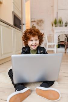 Little redhead boy uses a laptop