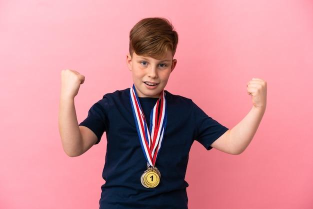 승리를 축하하는 분홍색 배경에 메달이 분리된 빨간 머리 소년
