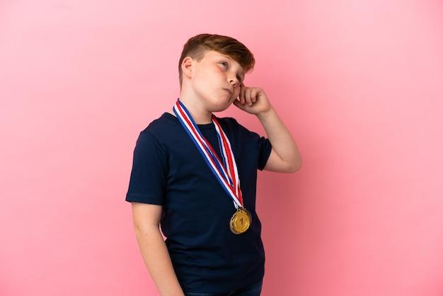 분홍색 배경에 격리된 메달을 가진 빨간 머리 소년은 의심을 갖고 얼굴 표정을 혼란스럽게 합니다. 프리미엄 사진