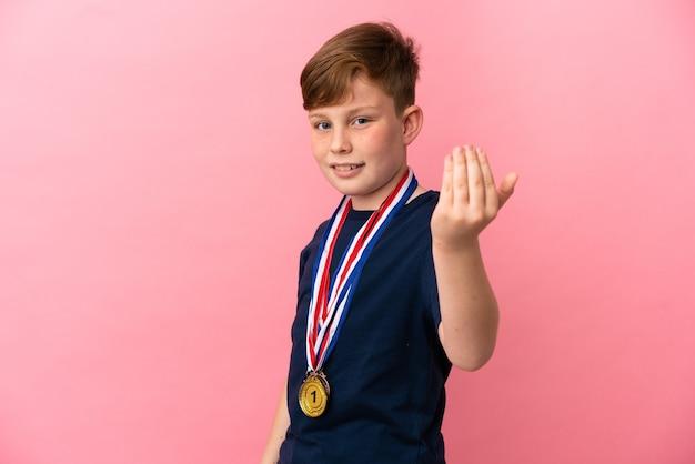 분홍색 배경에 격리된 메달을 가진 작은 빨간 머리 소년이 손을 잡고 초대합니다. 당신이 와서 행복