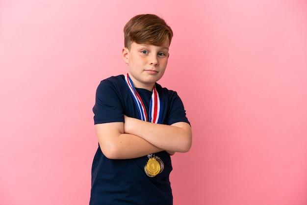 어깨를 들어 올리는 동안 의심 제스처를 만드는 분홍색 배경에 고립 된 메달을 가진 작은 빨간 머리 소년