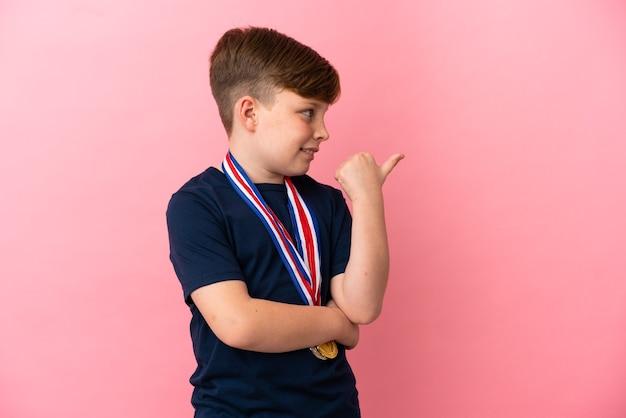 제품을 제시하기 위해 측면을 가리키는 분홍색 배경에 메달이 분리된 빨간 머리 소년