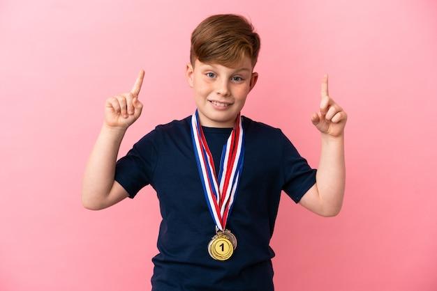 좋은 아이디어를 가리키는 분홍색 배경에 메달이 분리된 빨간 머리 소년