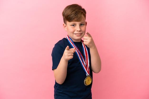 분홍색 배경에 고립 메달을 가진 작은 빨간 머리 소년은 자신감이있는 표정으로 손가락을 가리 킵니다.