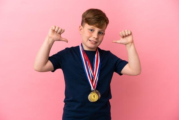 자랑스럽고 자기 만족스러운 분홍색 배경에 격리된 메달을 가진 작은 빨간 머리 소년