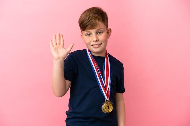 Маленький рыжий мальчик с медалями, изолированные на розовом фоне, салютуя рукой со счастливым выражением лица
