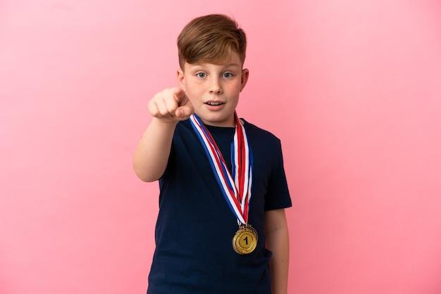 분홍색 배경 놀라게 하 고 앞을 가리키는에 고립 된 메달 작은 빨간 머리 소년