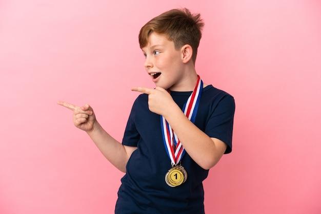 분홍색 배경에 격리된 메달을 가진 빨간 머리 소년은 놀라고 가리키는 쪽