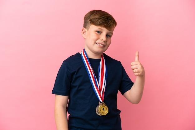 좋은 일이 일어났기 때문에 엄지손가락을 치켜들고 분홍색 배경에 메달이 분리된 빨간 머리 소년