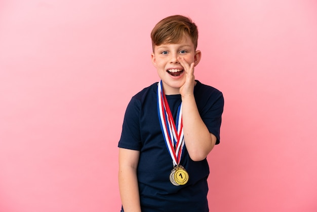 입 벌리고 외치는 분홍색 표면에 고립 된 메달 작은 빨간 머리 소년