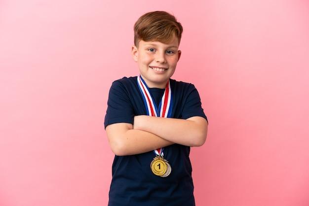 많이 웃 고 분홍색 표면에 고립 된 메달 작은 빨간 머리 소년