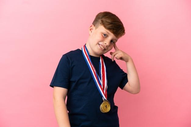 솔루션을 실현하려는 분홍색 벽에 고립 된 메달을 가진 작은 빨간 머리 소년