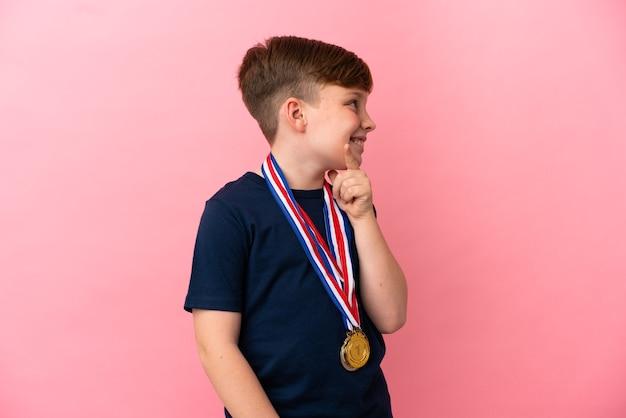 측면을 찾고 분홍색 벽에 고립 된 메달 작은 빨강 머리 소년