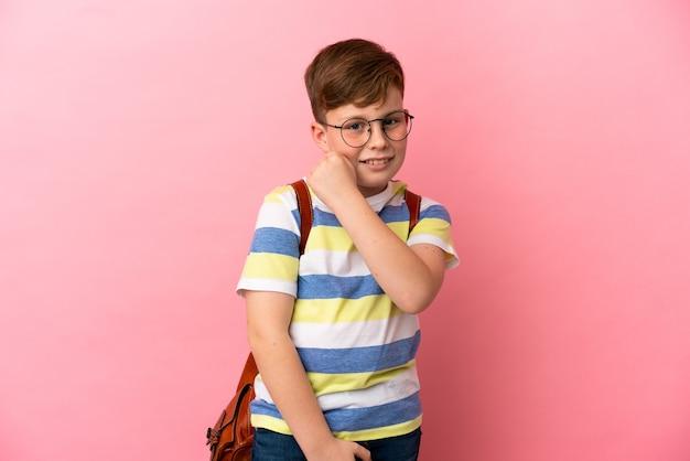 Маленький рыжий кавказский мальчик на розовом фоне празднует победу