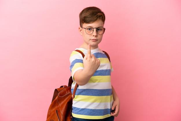 Маленький рыжий кавказский мальчик, изолированные на розовом фоне, делает приближающийся жест