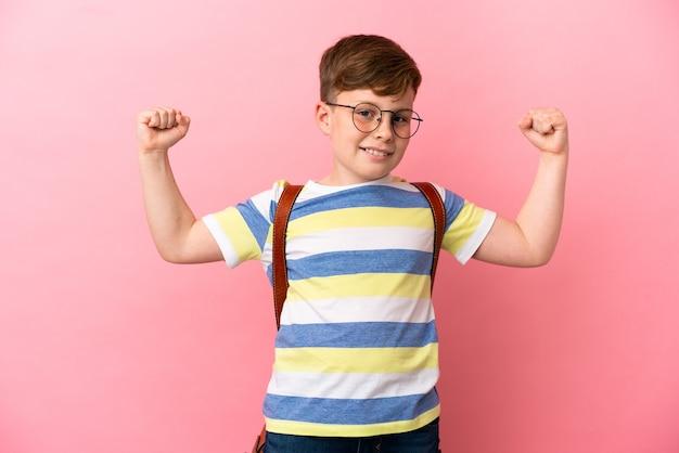 강한 제스처를 하 고 분홍색 배경에 고립 된 작은 빨간 머리 백인 소년