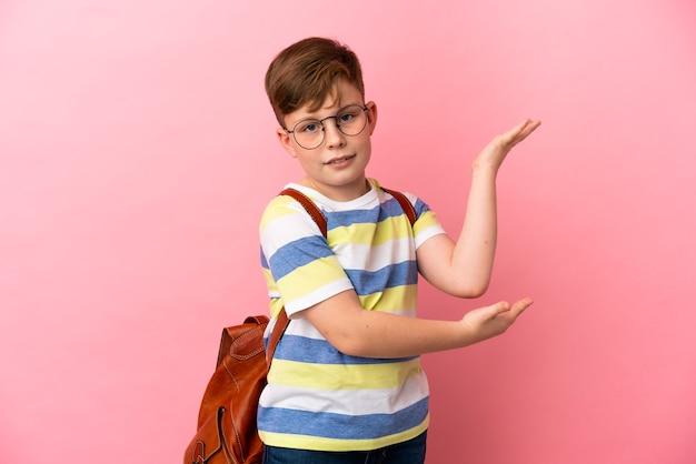 Маленький рыжий кавказский мальчик изолирован на розовом фоне, протягивая руки в сторону, приглашая прийти
