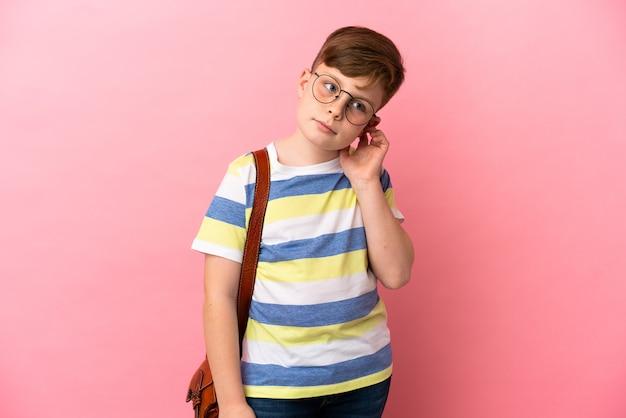 Маленький рыжий кавказский мальчик, изолированные на розовом фоне с сомнениями